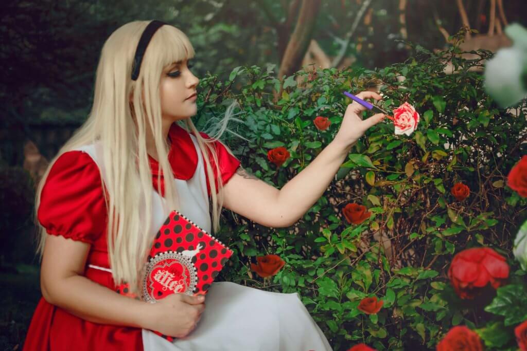 Desiree vestida de Alice pintando rosas no jardim
