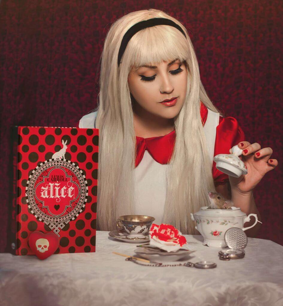 Desiree vestida de Alice servindo chá